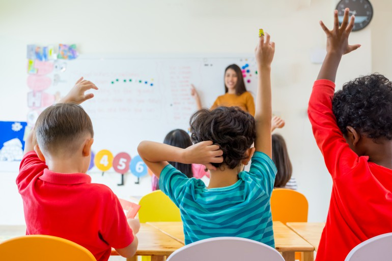 Preschool kid raise arm up to answer teacher question on whiteboard in classroom,Kindergarten education concept