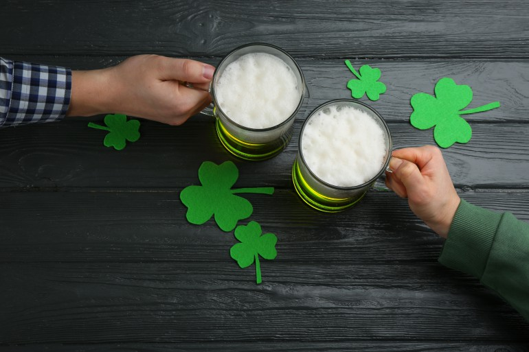 Man and woman toasting with green beer at black wooden table, top view. St. Patrick's Day celebration